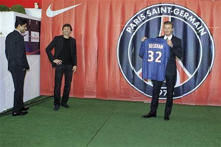 Soccer player David Beckham (R) presents his new jersey as he stands near Nasser Al-Khelaifi (L), Paris St Germain's club owner. (Reuters)