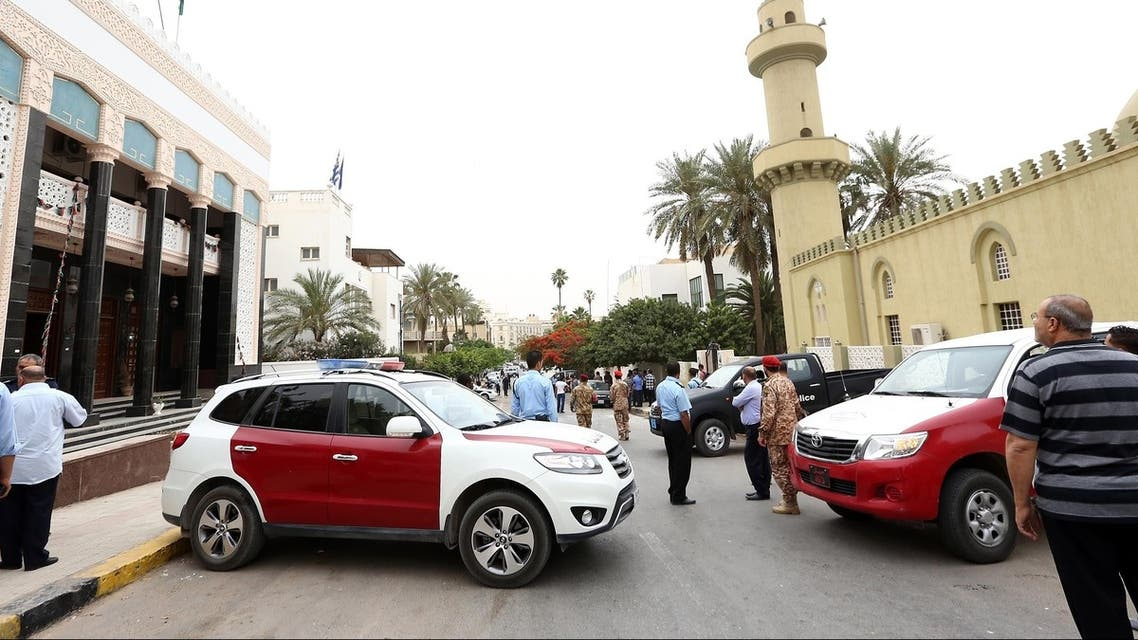 Libyan security forces and residents gather in a street housing the Algerian, Greek and Saudi embassies, where a bomb exploded lightly damaging a car on May 18, 2013 in Tripoli, Libya. (AFP)