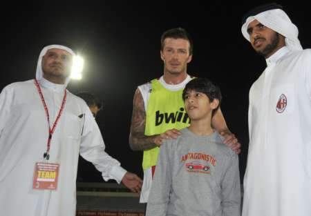 Italian soccer club AC Milan's new loan-signing David Beckham poses with fans after his first training session with the team at Al Nasr Stadium in Dubai, December 30, 2008. (Reuters)