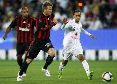 Al-Sadd's Mohammed Abdulraab (R) fights for the ball with AC Milan's David Beckham during the Jafal Rashed testimonial soccer match at the Jassim Bin Hamed stadium in Doha March 4, 2009. (Reuters)