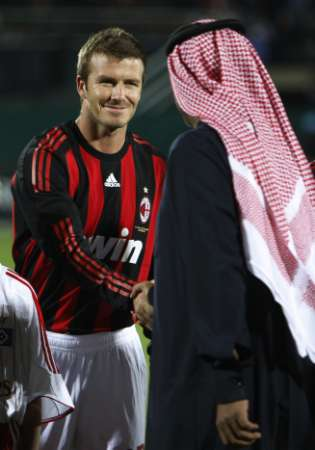 AC Milan's David Beckham greets an unidentified guest ahead of his friendly soccer match against Hamburg SV in Dubai, January 6, 2009. (Reuters)