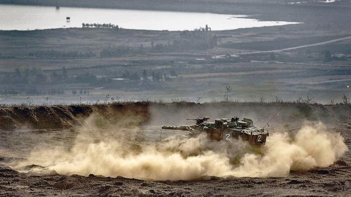 An Israeli Merkava tank maneuvers on the Israeli annexed Golan Heights overlooking the Syrian village of Breqa AFP