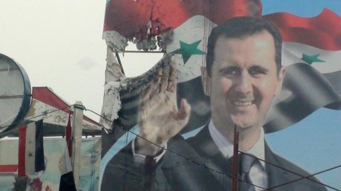 A poster depicting Syria's President Bashar Assad is seen damaged in Duma, near Damascus, 25 January 2012. (Photo: Reuters