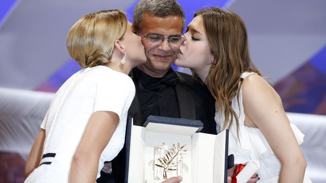 """French actresses Lea Seydoux (L) and Adele Exarchopoulos kiss French-Tunisian director Abdellatif Kechiche after he was awarded on May 26, 2013 with the Palme d'Or for the film """"Blue is the Warmest Colour"""" during the closing ceremony of the 66th Cannes film festival in Cannes."""