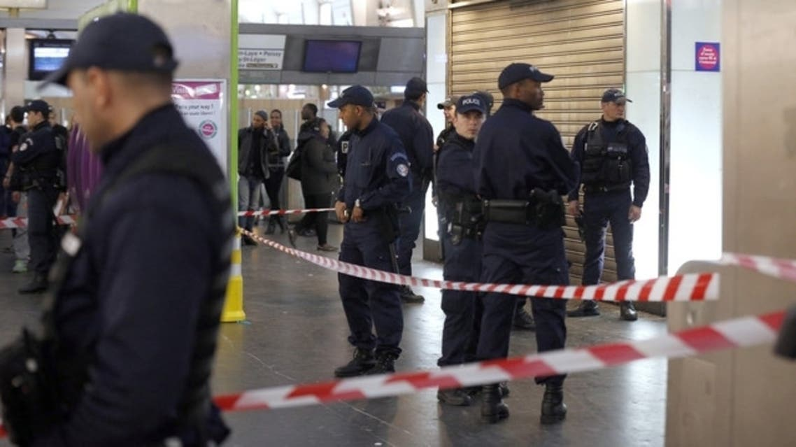 Police officers stand at the site where a man attacked a French soldier patrolling a Metro-station mall on the western edge of Paris. (AFP)