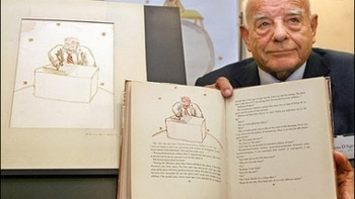 """Francois D'Agay, nephew of late French author Antoine de Saint-Exupery displays a page of the book """"The Little Prince Aviator."""" (AFP)"""