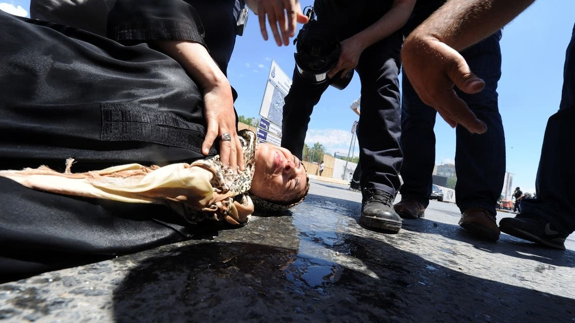 A woman lays on the ground on June 1, 2013 during clashes with riot police against the demolition of Taksim Gezi Park in Istanbul. (AFP)