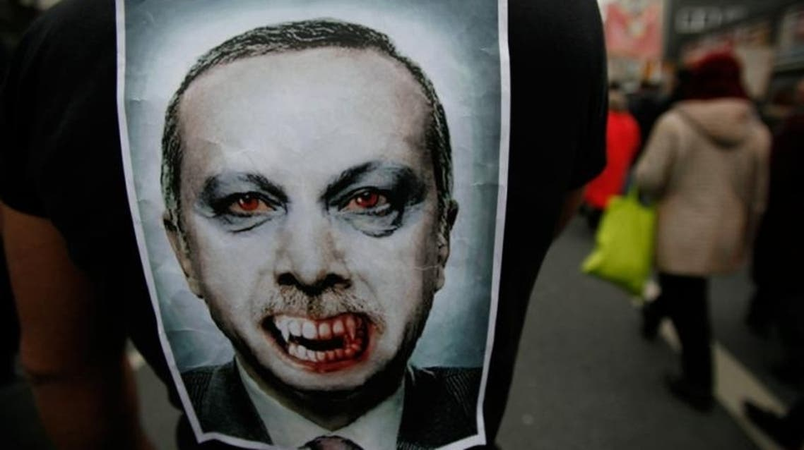 Turkish Prime Minister Recep Tayyip Erdogan is depicted as a vampire in a picture pinned on the back of a protestor during a demonstration of several thousand Alevites in the western German city of Bochum 17 March 2012.