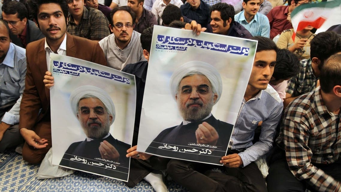 Iranian supporters hold a poster featuring Hassan Rowhani, a moderate Iranian presidential candidate, during an election campaign at the Jamaran mosque in Tehran, on June 1, 2013. (File Photo: AFP)