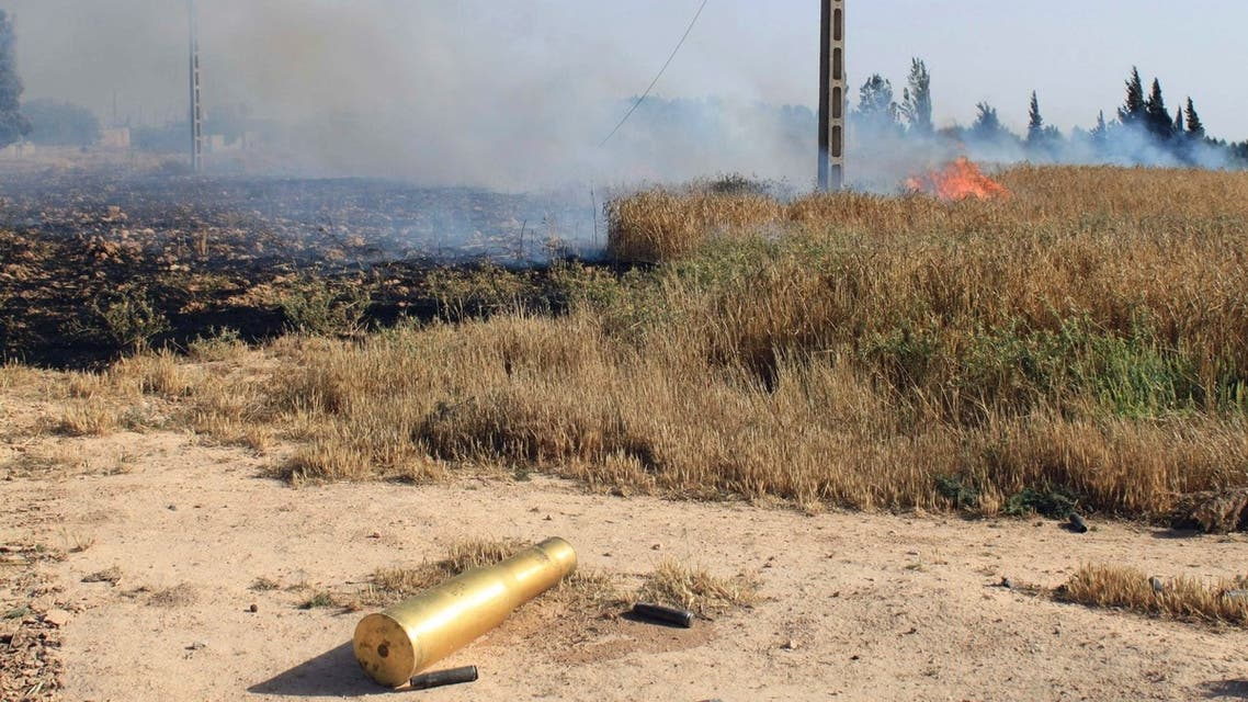 An empty ammunition casing and a fire are seen in a field after heavy fighting between Free Syrian Army fighters, and the forces of Syrian President Bashar al-Assad and Lebanon's Hezbollah at the al Barak area near Qusair town May 31, 2013. (REUTERS)