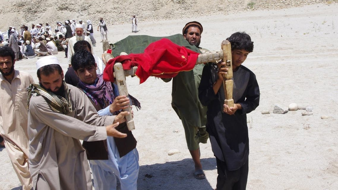 Afghan men carry the body of a victim of a suicide attack at Mehtarlam city, capital of Laghman province on June 3, 2013.