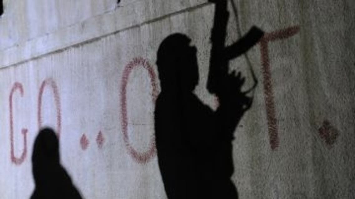 The shadows of armed Free Syrian Army rebels are seen on a wall at the entrance to the north Syrian city of Binnish on Feb. 15, 2012. (Bulent Kilic /AFP/Getty Images)