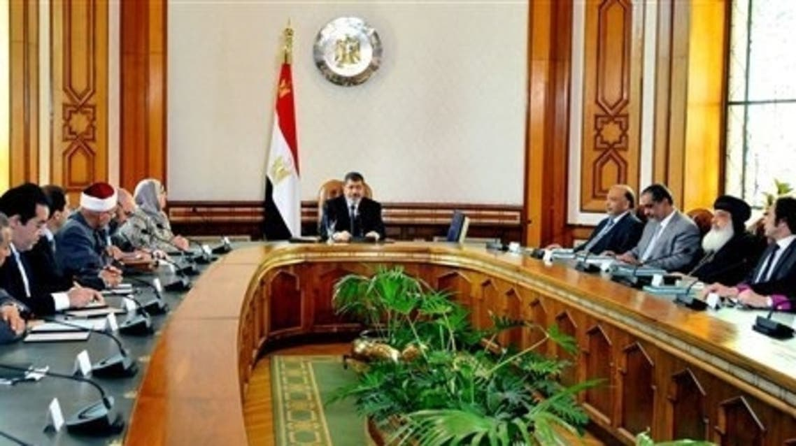 In this image released by the Egyptian Presidency, Egyptian President Mohammed Morsi, center, meets with politicians at the Presidential Palace in Cairo, Egypt, Monday, June 3, 2013.  (Photo courtesy: AP)