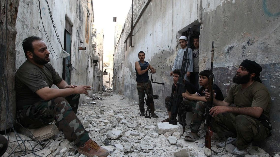Members of the Free Syrian Army talk as they sit with their weapons in a damaged street in Aleppo's Karm al-Jabal district, June 3, 2013. Reuters