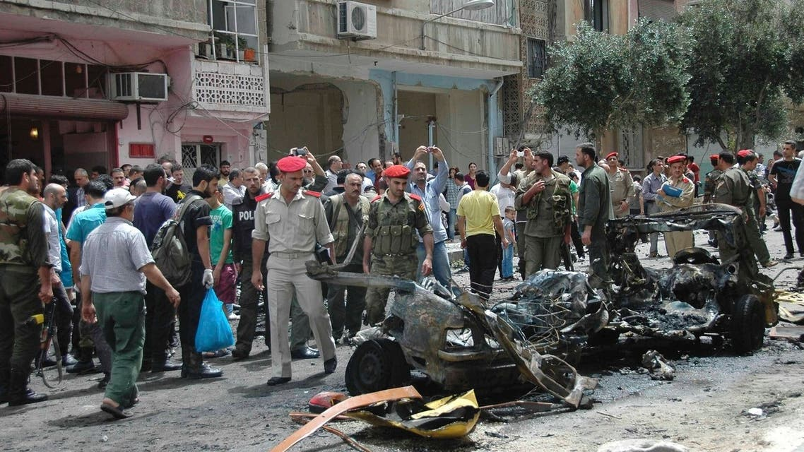 People look at the wreckage of a vehicle after a suicide car bomb exploded in the al-Adaweya district of Homs June 8, 2013 REUTERS