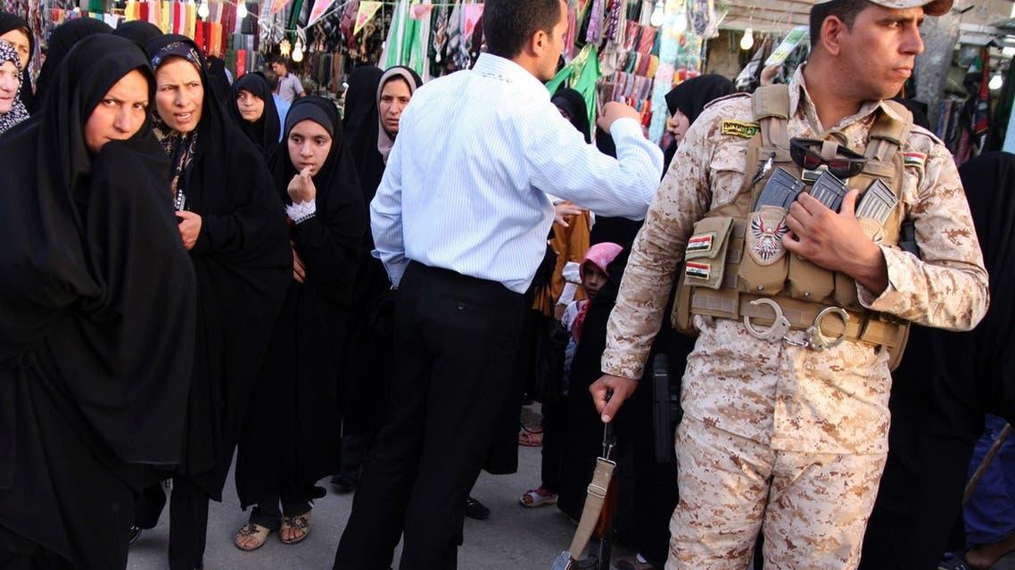 Iranian Shiite Muslim pilgrims walk past a member of Iraq's security personnel in Kerbala, 110 km south of Baghdad, June 7, 2013. (Reuters)