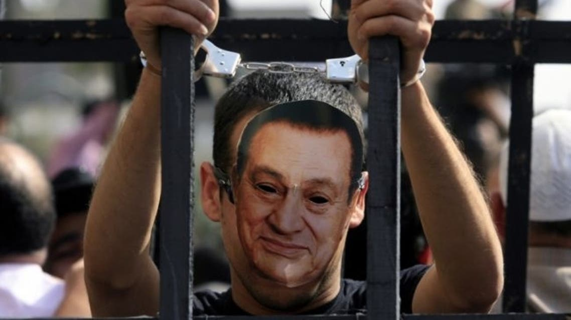 An Egyptian protester wearing the mask of ousted Egyptian president Hosni Mubarak stands with handcuffs inside a makeshift prison cell at Cairo's Tahrir Square on April 8, 2011 during a demonstration attended by tens of thousands of Egyptians. (Misam Saleh/AFP/Getty Images)