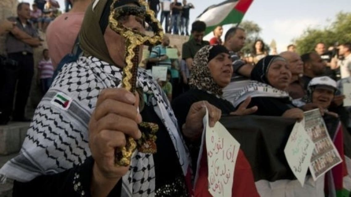 A Palestinian woman holds a symbolic key during a rally to mark the 46th anniversary of Israel's occupation of the West Bank and Gaza Strip, on June 5, 2013 at Damascus Gate in Jerusalem. (AFP)