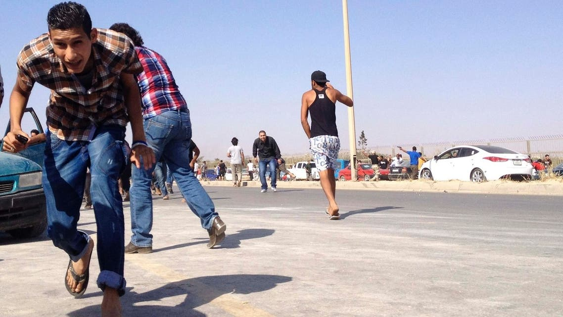 Protesters run for cover during an attack on a Libyan militia, the Libya Shield brigade, headquarters in Benghazi, June 8, 2013.
