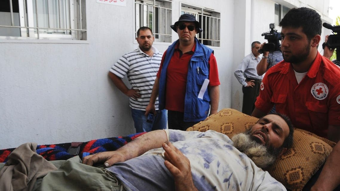 Lebanese Red Cross personnel transport a Syrian refugee injured in the fighting between Syrian government troops and rebel fighters in the Syrian border town of Qusair, to a hospital in Jib-Janine town, Bekaa Valley June 8, 2013. (Reuters)
