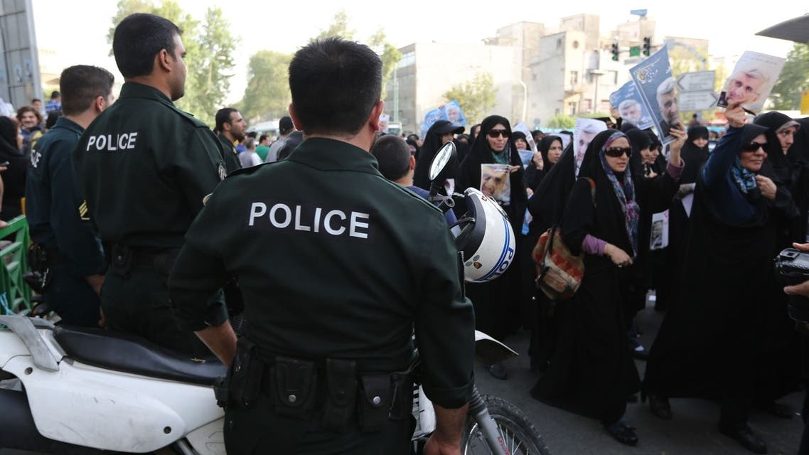 Iranian police watch as female supporters of Iranian presidential candidate and lead nuclear negotiator Saeed Jalili hold up his image during a campaign rally along Valiasr Street in the Iranian capital Tehran, on June 9, 2013. (AFP)