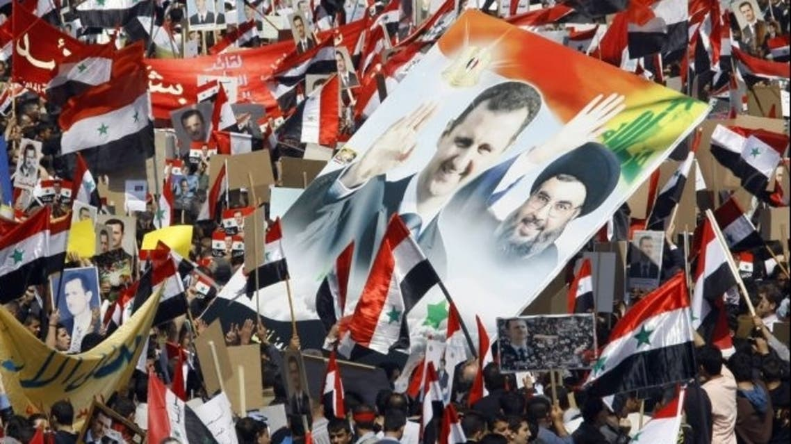 Syrians hold portraits of President Bashar al-Assad (Left) and Lebanon's Hezbollah chief Hassan Nasrallah (Right) during a rally. Hezbollah is losing support due to its unwavering support for the Syrian regime and the political fall-out of the Syrian uprising is deepening the political divides in Lebanon. (ANWAR AMRO/Stringer/AFP/Getty Images)