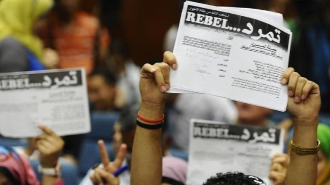 "Protesters opposing Egyptian President Mohammad Mursi hold up documents from the ""Tamarod"" campaign during a news conference at their headquarters in Cairo May 29, 2013. (Reuters)"