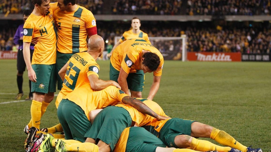 Robbie Kruse (under players) of Australia is jumped on by teammates after scoring the third goal during their World Cup qualifying soccer match against Jordan at Etihad Stadium, Melbourne June 11, 2013. (Reuters)