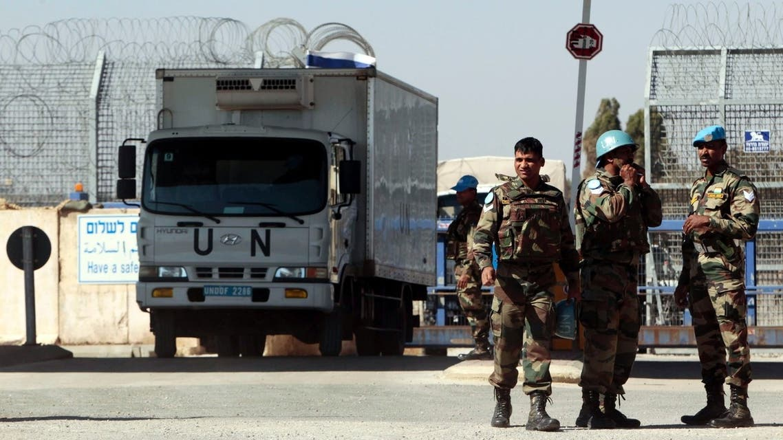 U.N. peacekeeping soldiers stand near vehicles at the Quneitra border crossing between Israel and Syria, in the Israeli-occupied Golan Heights June 11, 2013. (Reuters)