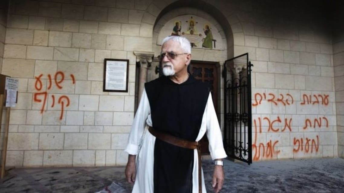 """A priest walks between graffiti reading in Hebrew, """"Jesus is a monkey"""" (L), which was sprayed on the wall of the Christian monastery near Jerusalem, September 4, 2012. AFP"""