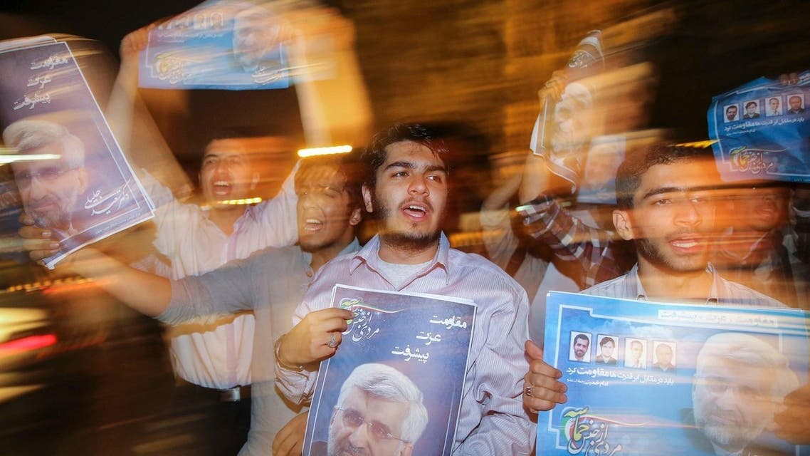 Supporters carry campaign posters for Iranian presidential candidate Saeed Jalili on the streets of Tehran June 12, 2013.