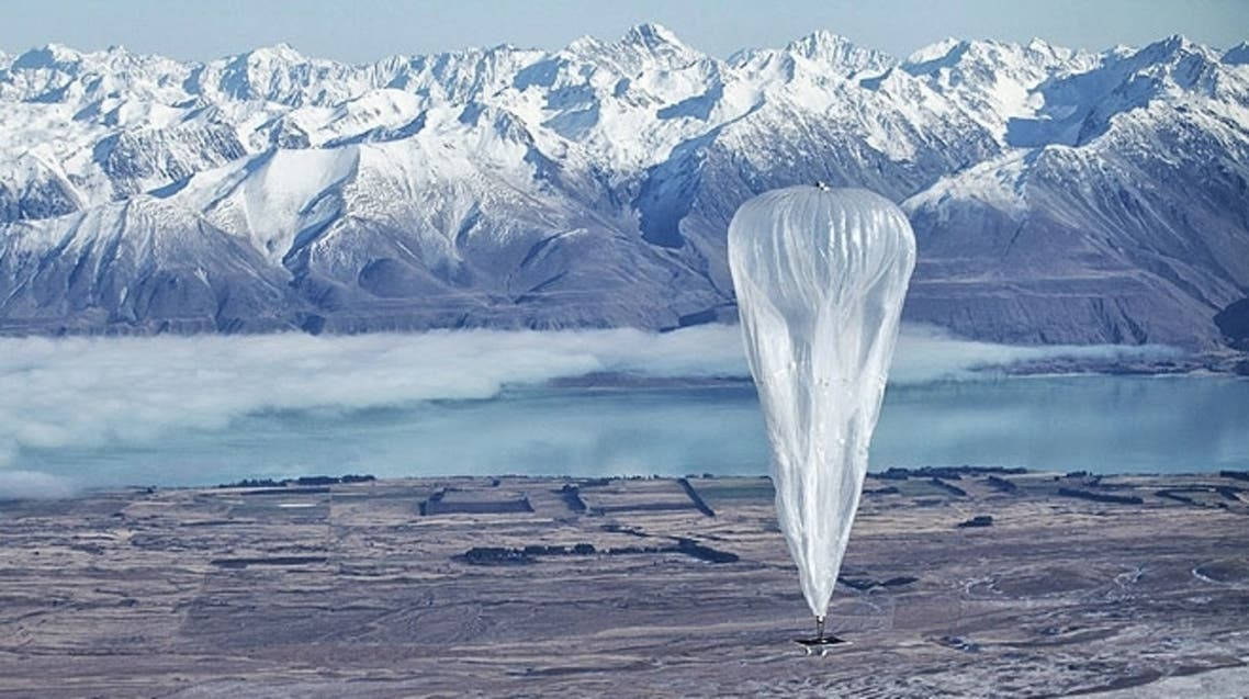 A Google balloon sails through the air in Tekapo, New Zealand with the Southern Alps mountains in the background.