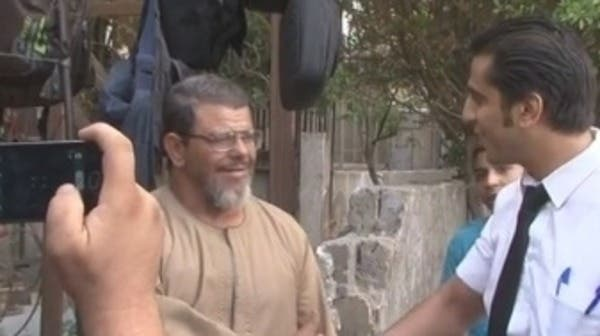 People greet and take pictures with Egyptian President Mohammed Mursi's look-alike. (Al Arabiya)