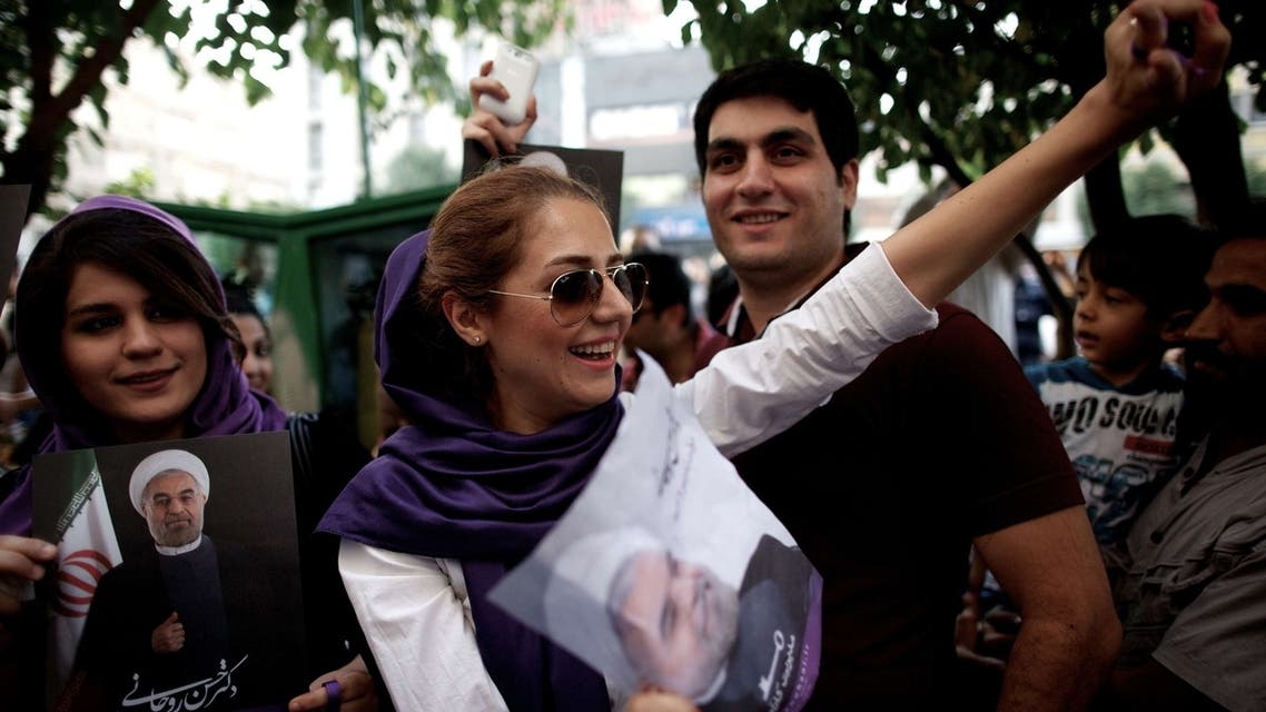 Iranians celebrate the victory of moderate presidential candidate Hassan Rowhani (portrait) in the Islamic Republic's presidential elections in downtown Tehran on June 15, 2013. (Reuters)