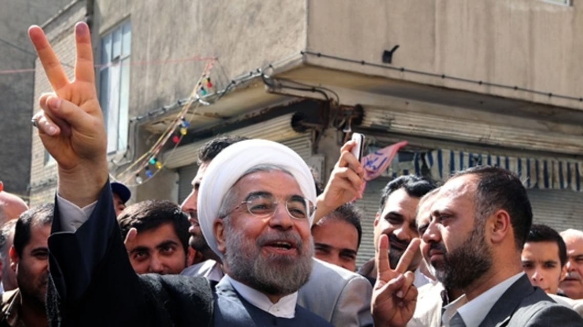 Iranian moderate presidential candidate, Hassan Rowhani (C) flashes the sign of victory as he leaves a polling station after voting on in Tehran during the first round of the presidential candidate. (AFP)