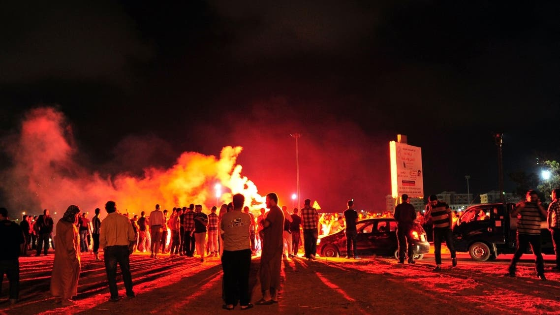 Protesters block the road and set off fireworks, after they burned two vehicles belonging to the Libyan Army's First Infantry Brigade in Benghazi June 14, 2013.