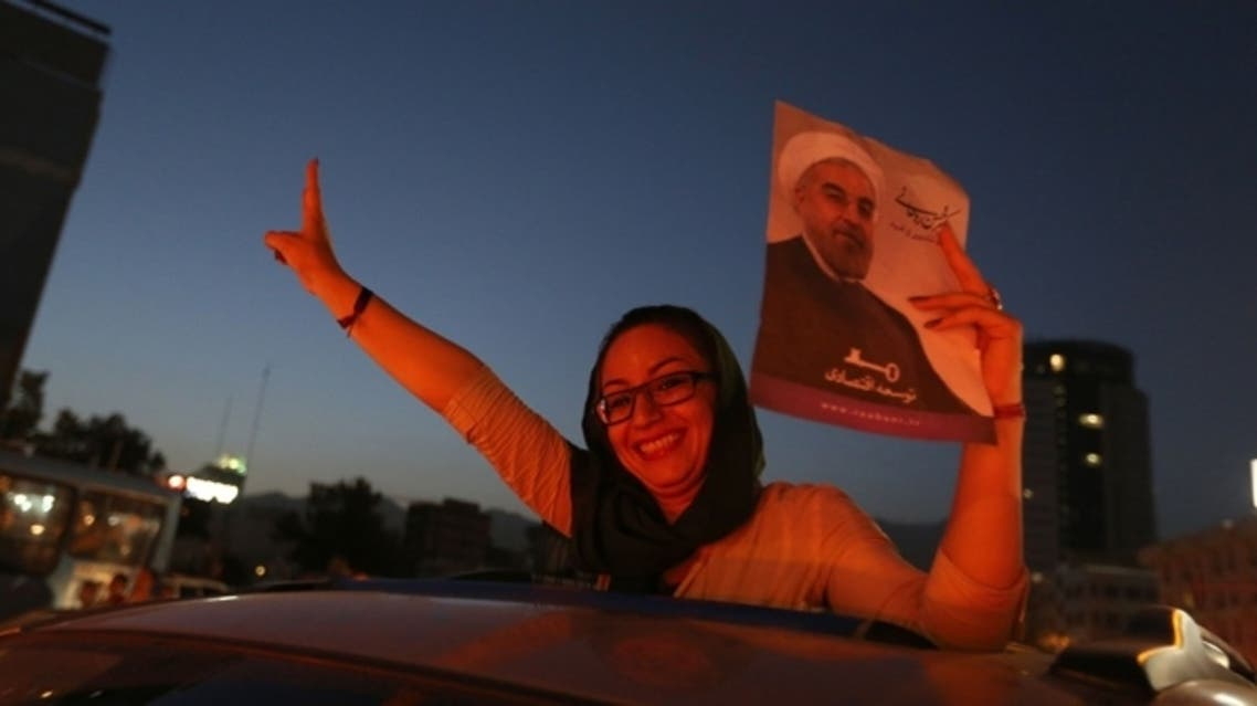 An Iranian woman celebrates the victory of moderate presidential candidate Hassan Rowhani (portrait) in the presidential elections at Vanak Square, in northern Tehran, on June 15, 2013. (AFP)