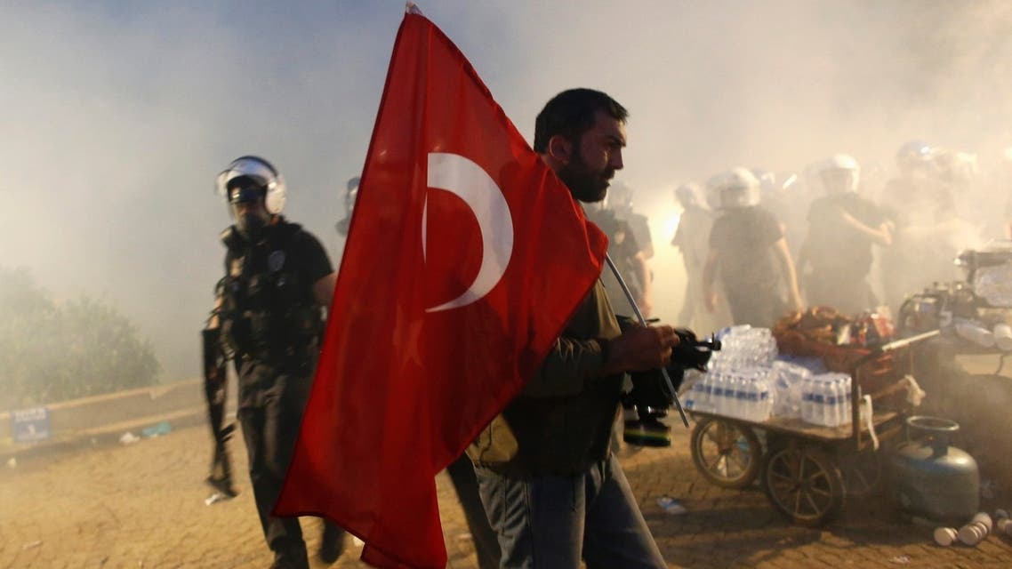 A protester holds a Turkish flag as riot police order them to evacuate Gezi Park in central Istanbul June 15, 2013. (Reuters)