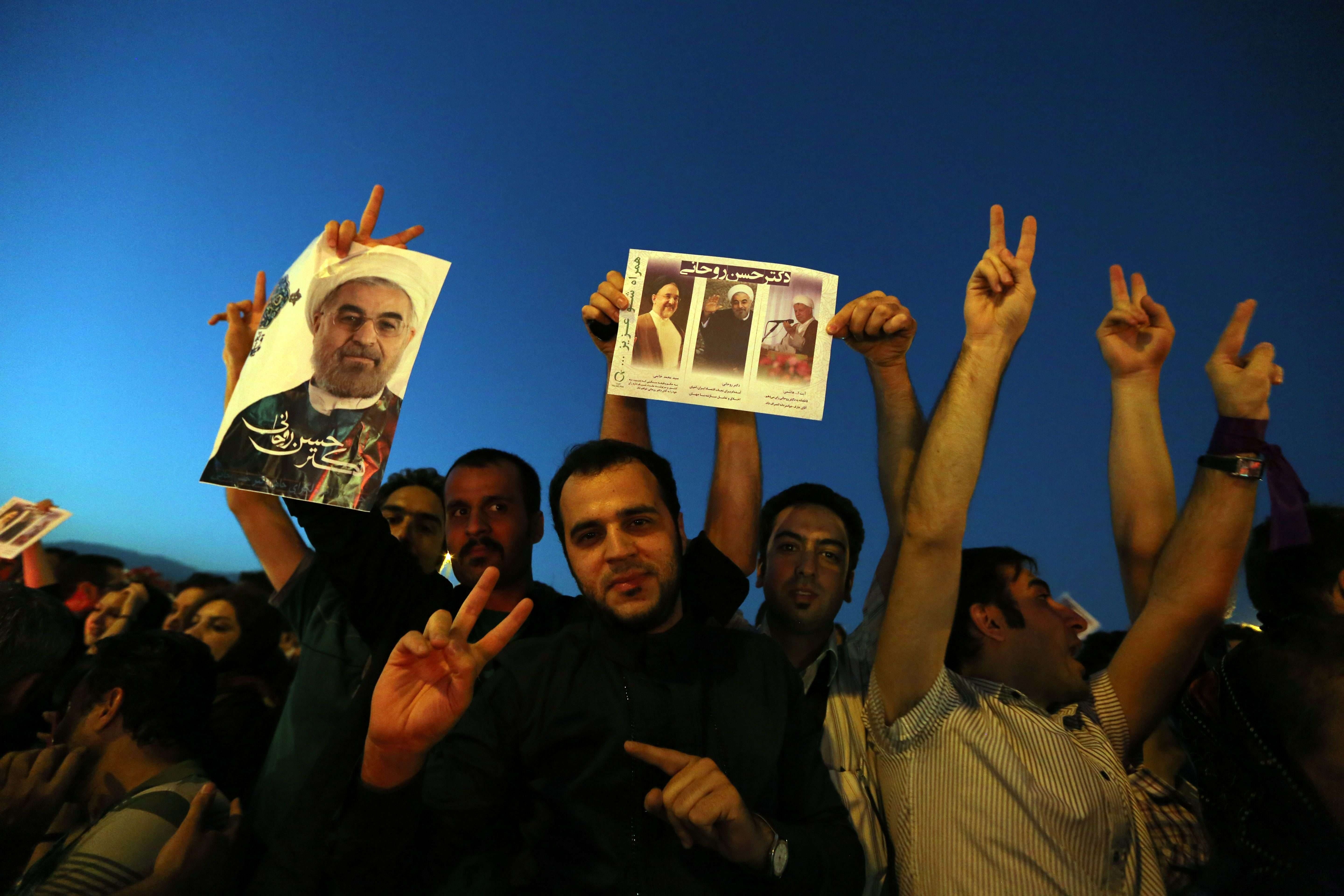 Iranians celebrate the victory of moderate presidential candidate Hassan Rowhani (portrait) in the presidential elections at Vanak Square, in northern Tehran, on June 15, 2013. (AFP)