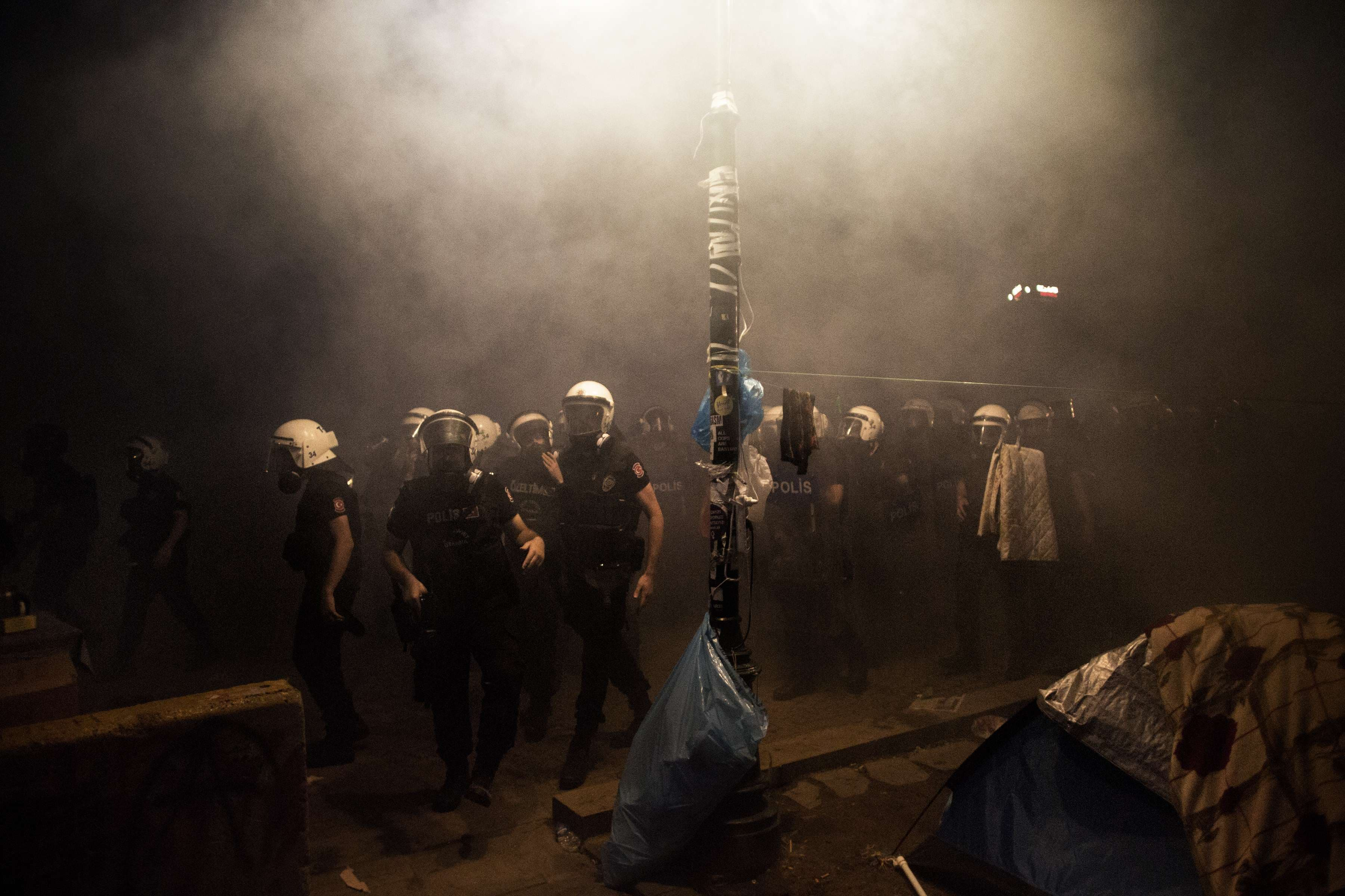 Under the cover of a cloud of tear gas Turkish riot police officers arrive to chase out demonstrators and to dismantle the tent camp set up by demonstrators in Gezi Park in Istanbul on June 15, 2013. (AFP)