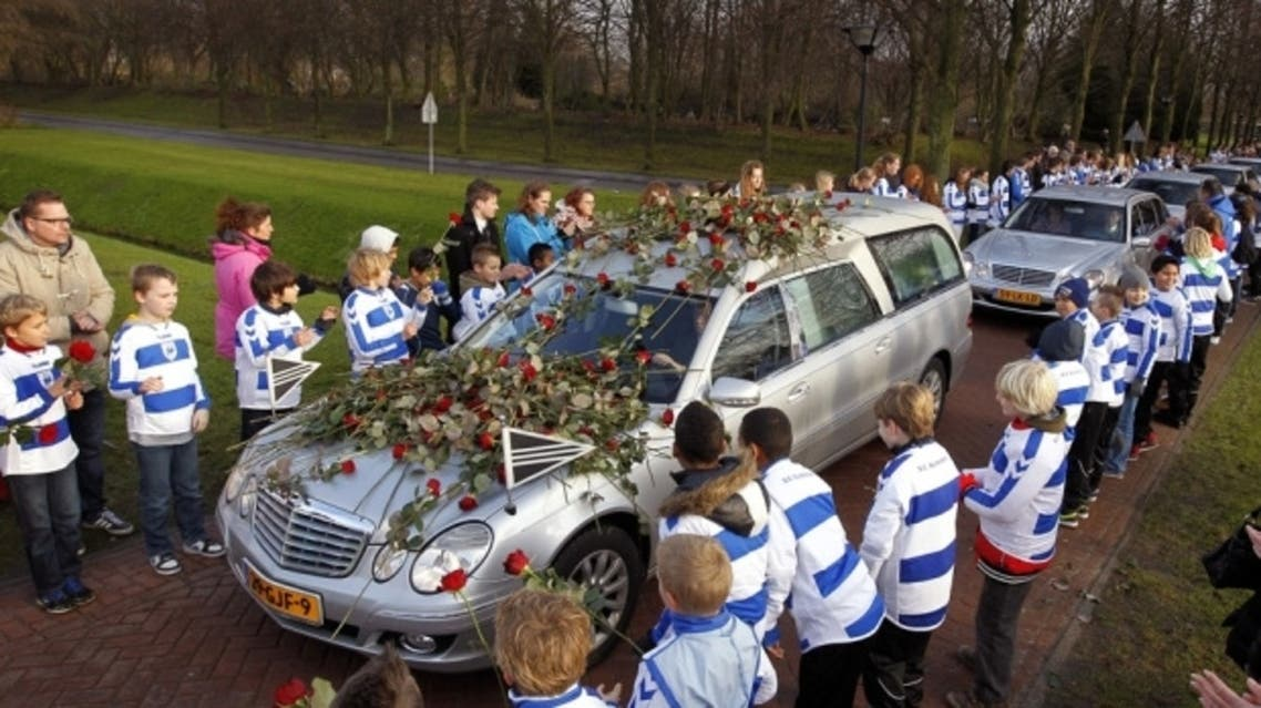 Members of Dutch football club SC Buitenboys wearing the colors of the club stand to they pay respect to Dutch linesman Richard Nieuwenhuizen as the hearse carrying the body of Nieuwenhuizen arrives at the crematory. (File Photo: AFP)