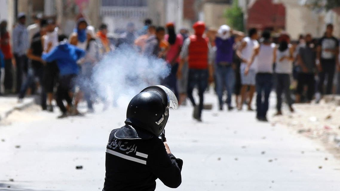 A riot police officer fires teargas during clashes with supporters of Islamist group Ansar al-Sharia in Tunis on May 19. (Reuters)