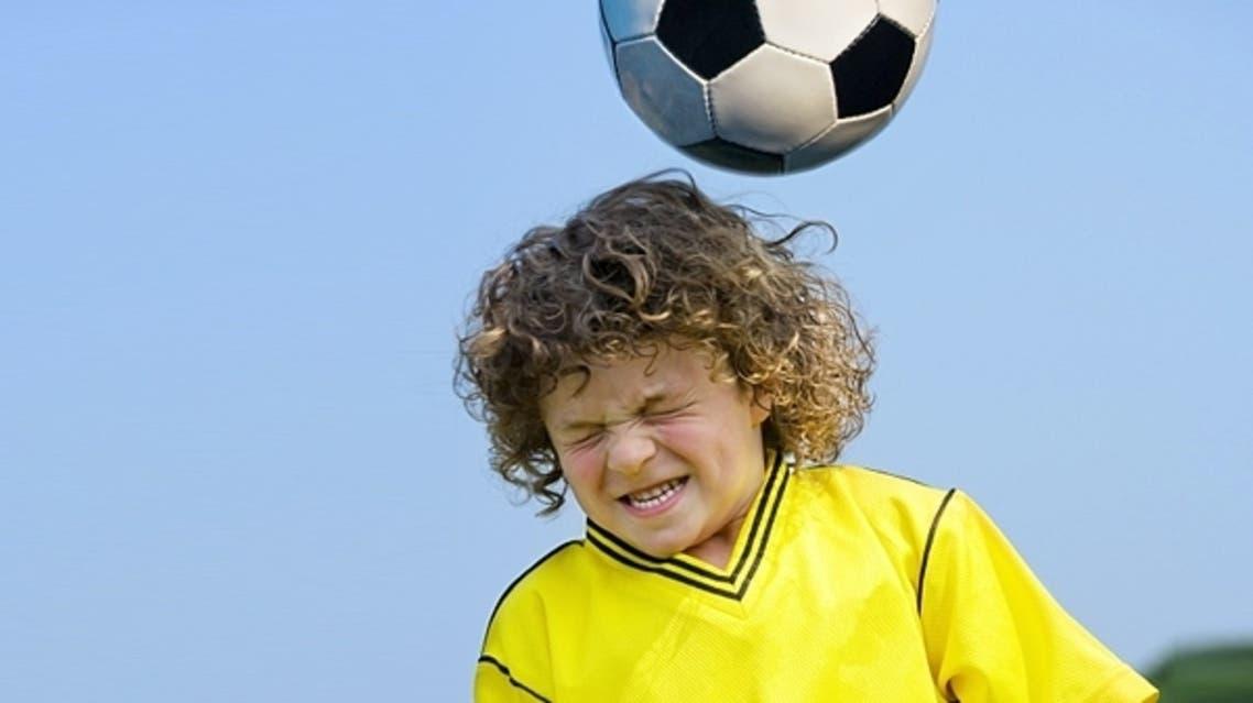طفل يضرب الكرة برأسة
