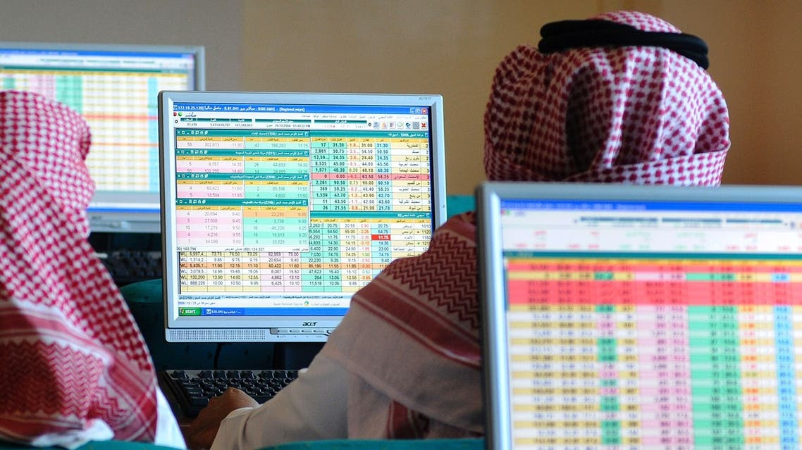 Saudi traders monitor stocks at a Saudi Bank in Dammam. A change in the weekend timing is expected to give a boost to business, economists say. (File photo: Reuters)