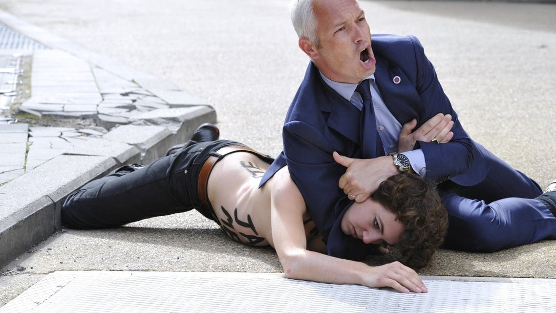 A security guard tackles to the ground a Femen activist as she tried to stop the car of Tunisian Prime Minister from leaving the EU commission building on June 25, 2013 at the EU headquarters in Brussels. (AFP)