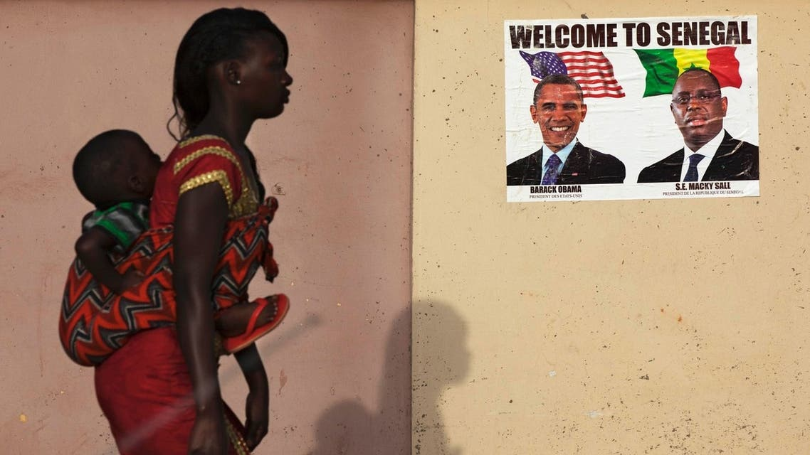 A woman carrying her baby on her back walks past a poster of U.S. President Barack Obama and Senegal's President Macky Sall before Obama's visit in Dakar June 26, 2013. (File photo: Reuters)