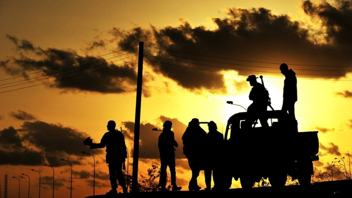 Libyan rebel fighters are silhouetted at sunset on March 7, 2011 in the oil center of Brega. AFP