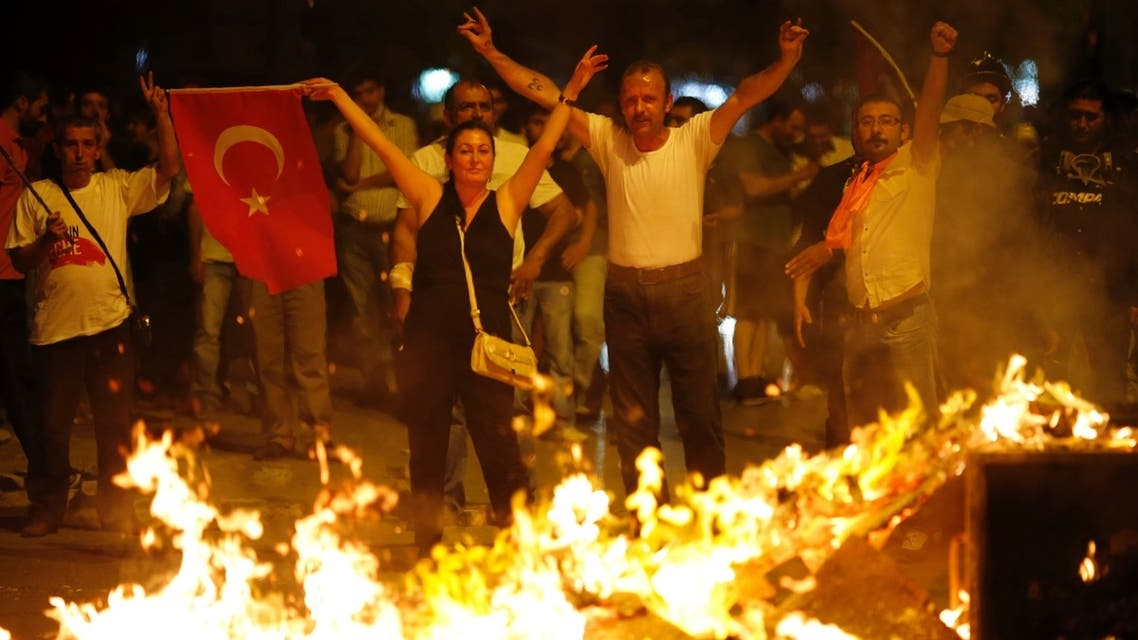 Anti-government protesters make V-signs and wave a flag as they block a road during a demonstration in Ankara early June 26, 2013. REUTERS
