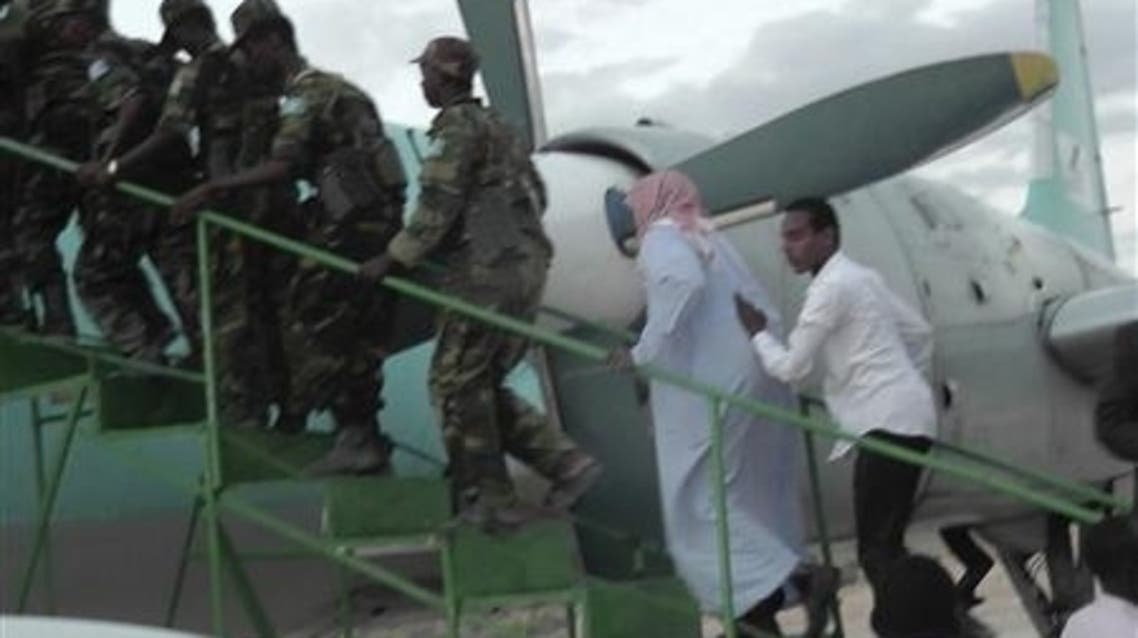Sheikh Hassan Dahir Aweys (2nd R), one of Somalia's most prominent Islamist rebel commanders, who was arrested on Wednesday, is escorted at Adado airstrip June 29, 2013, to be transferred to capital Mogadishu. (Reuters)