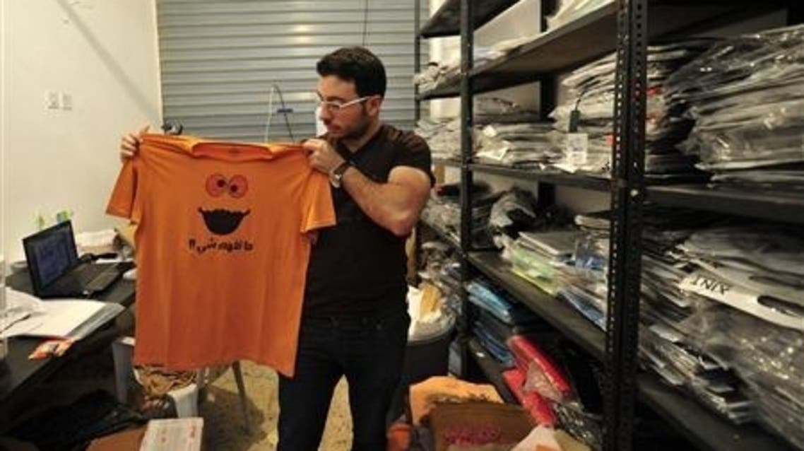 An employee holds up a t-shirt at the popular clothing store Boza in Benghazi June 26, 2013. (Reuters)